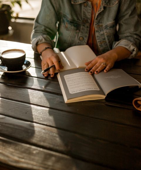 Close up of a white person in a denim jacket writing in a book while drinking a cup of coffee